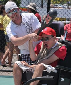 Man helping boy in wheelchair to bat