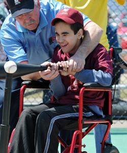 Boy in wheelchair batting